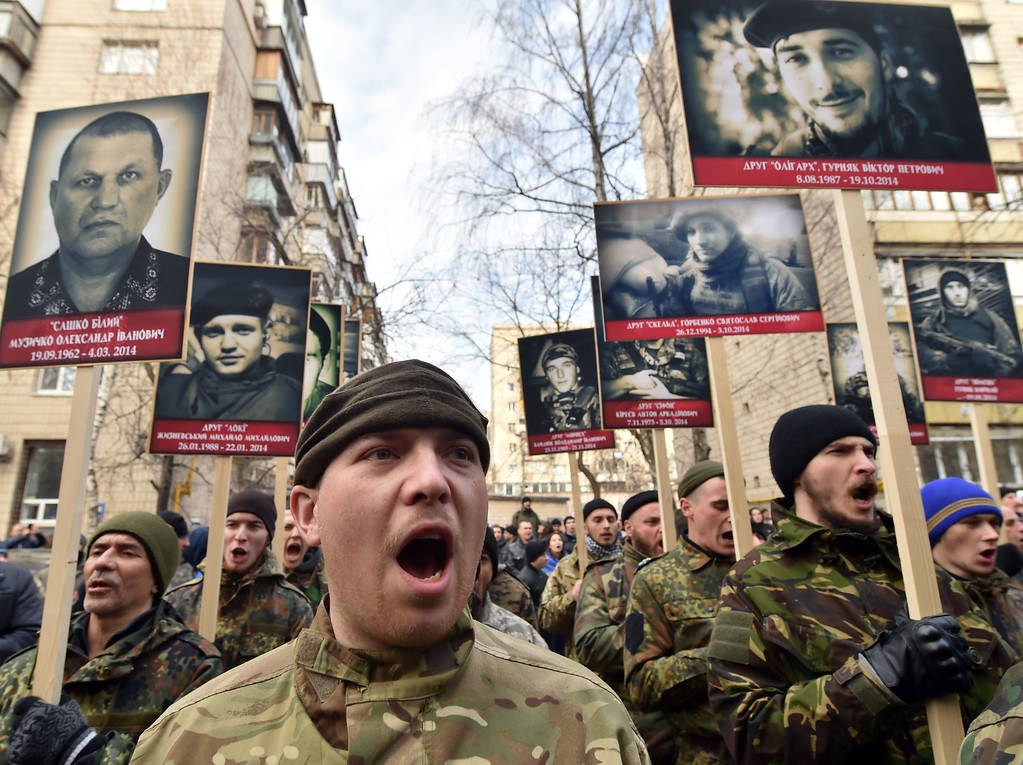 ". Fighters of the Ukrainian volunteers\' battalions and activists of the Right Sector Party carry portraits of their friends killed in the east of Ukraine as they shout slogans ""Donbass is Ukraine!\"", \""Crimea is Ukraine!\"", \""Glory for the heros\"" during their \""March of Truth, March of Rights \"" in Kiev, on February 25, 2015. The activists are demanding more decisive actions towards the east of the country where a 10-month conflict has been ragging between pro-Russia separatist and Ukrainian forces. SERGEI SUPINSKY/AFP/Getty Images"