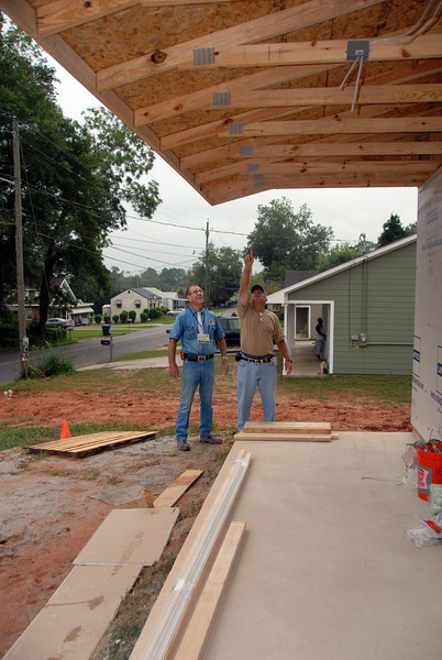 Volunteer Bob Crowley is amazed at the structure of the truss-style overhang of the porch. mlj
