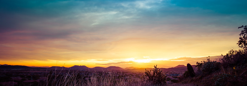 Colorful Panorama of the Sun Setting Over a Desert Landscape