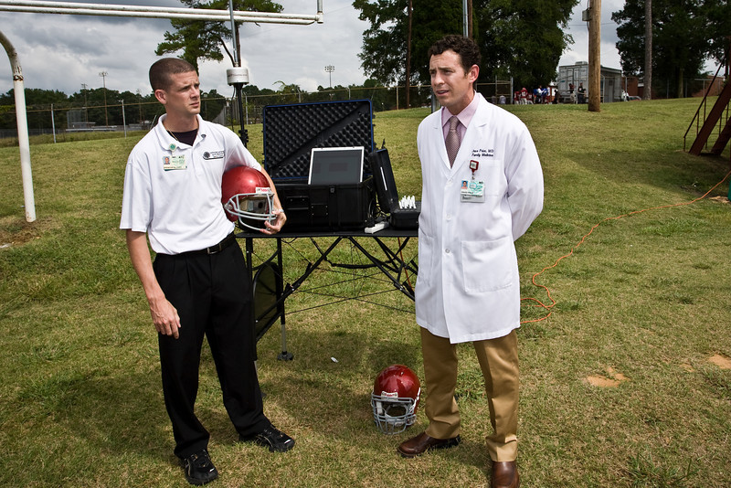 Spencer Elliott, ATC and David Price, MD, discuss the new football helmet with sensor equipment to be used by West Meck HS.