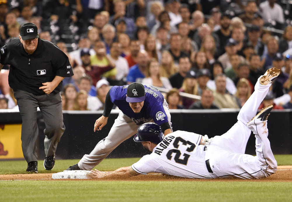 . Yonder Alonso #23 of the San Diego Padres slides into third base ahead of the tag of Nolan Arenado #28 of the Colorado Rockies as umpire Dana DeMuth makes the call  during the sixth inning of a baseball game at Petco Park August, 11, 2014 in San Diego, California.  (Photo by Denis Poroy/Getty Images)