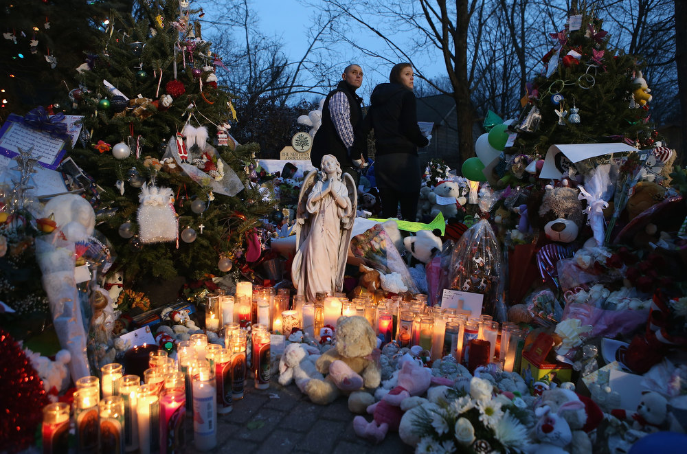 . Mourners visit a streetside memorial for 20 children who were killed at Sandy Hook Elementary School on December 20, 2012 in Newtown, Connecticut. Six funeral services were held Thursday in the Newtown area for students and teachers slain in the attack.  (Photo by John Moore/Getty Images)