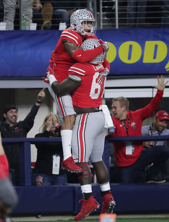 . Ohio State safety Damon Webb (7) is lifted by defensive lineman Robert Landers (67) after Webb scored a touchdown on an interception during the first half of the Cotton Bowl NCAA college football game against Southern California in Arlington, Texas, Friday, Dec. 29, 2017. (AP Photo/LM Otero)