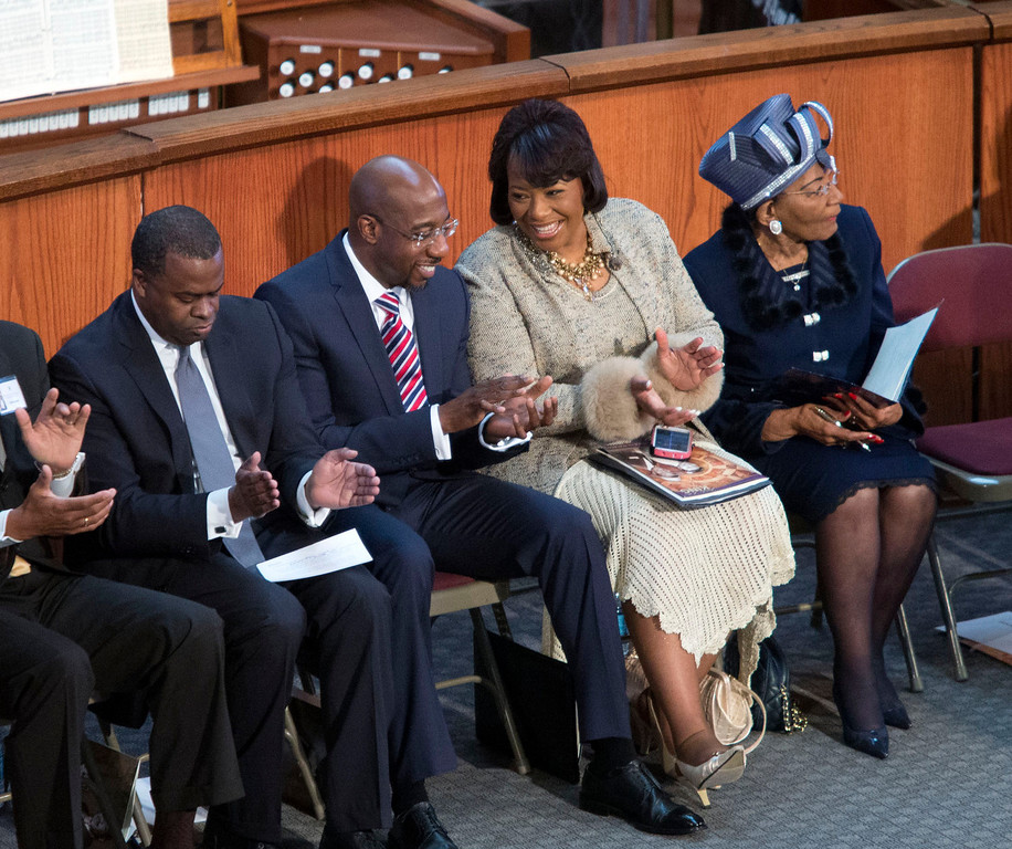 . Bernice King, second from right, talks with pastor Raphael Warnock, second from left, during the Rev. Martin Luther King Jr. holiday commemorative service at Ebenezer Baptist Church Monday, Jan. 20, 2014, in Atlanta. Bernice King is the daughter of the late Dr. Martin Luther King Jr., and Christine King Farris, right, is the only living sibling of the late Dr. Martin Luther King Jr.. Also pictured is Atlanta mayor Kasim Reed, left. (AP Photo/Jason Getz)