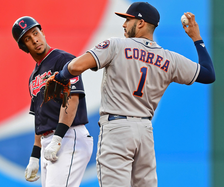 . Cleveland Indians\' Michael Brantley looks over at Houston Astros\' Carlos Correa after Brantley hit a double during the third inning of a baseball game Friday, May 25, 2018, in Cleveland. (AP Photo/David Dermer)