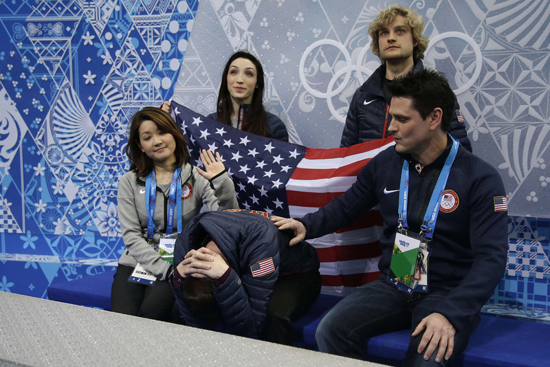 ". US Jeremy Abbott (C) is comforted by his team in the ""kiss and cry\"" zone after performing in the Men\'s Figure Skating Team Short Program at the Iceberg Skating Palace during the Sochi Winter Olympics on February 6, 2014. (DARRON CUMMINGS/AFP/Getty Images)"