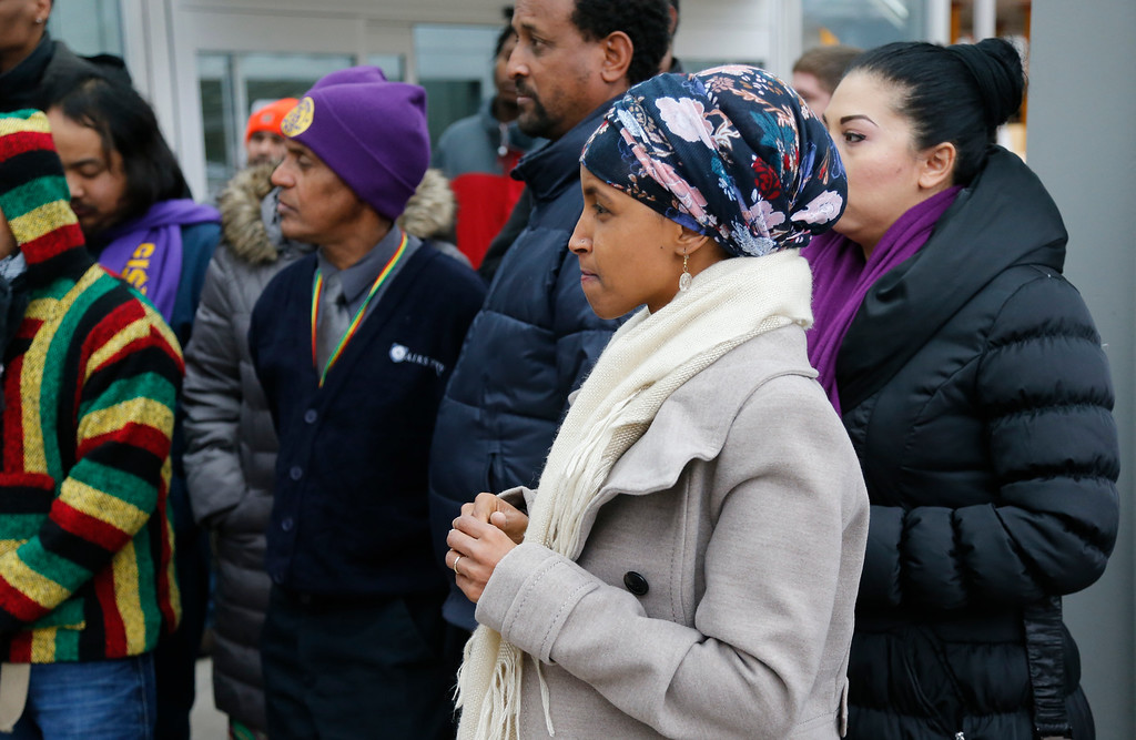 . Ilhan Omar, right, the first Somali-American elected to a state legislature, waits to speak during a rally including airport workers Tuesday, Nov. 29, 2016, at the Minneapolis-St. Paul International Airport in Minneapolis in support of efforts calling for $15 minimum wages. Omar was elected to the Minnesota House. (AP Photo/Jim Mone)