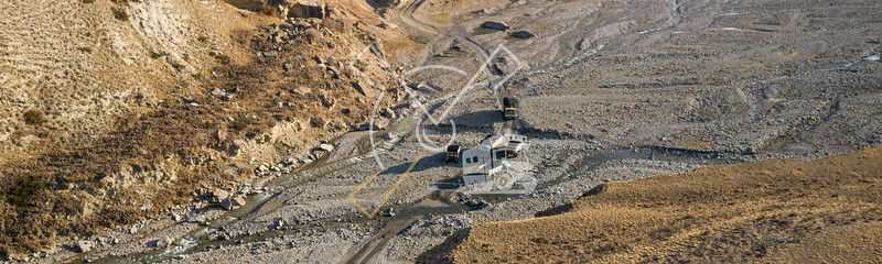 aerial image showing trucks traffic coming from the coal mine crossing the river bed in the Arpa valle
