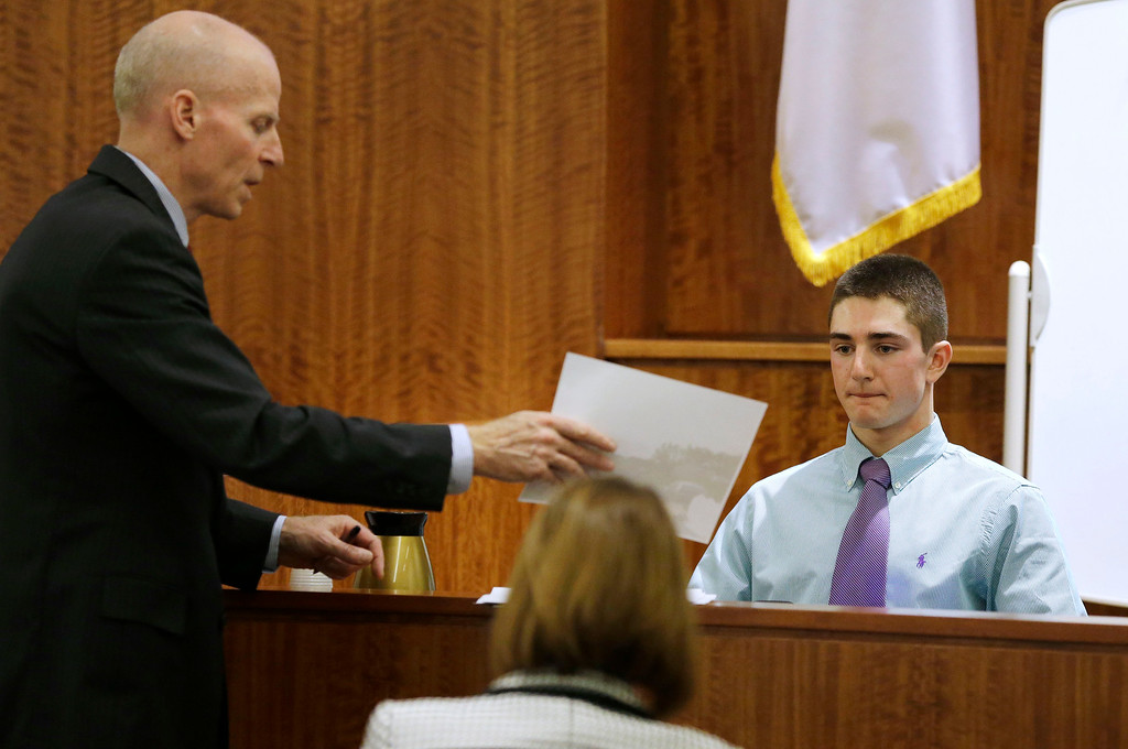 . William McCauley, left, assistant district attorney, shows witness Matthew Kent, right, a photograph as he testifies during the murder trial for former New England Patriots football player Aaron Hernandez, Thursday, Jan. 29, 2015, in Fall River, Mass. Hernandez is charged with killing semiprofessional football player Odin Lloyd, 27, in June 2013.  (AP Photo/Steven Senne, Pool)