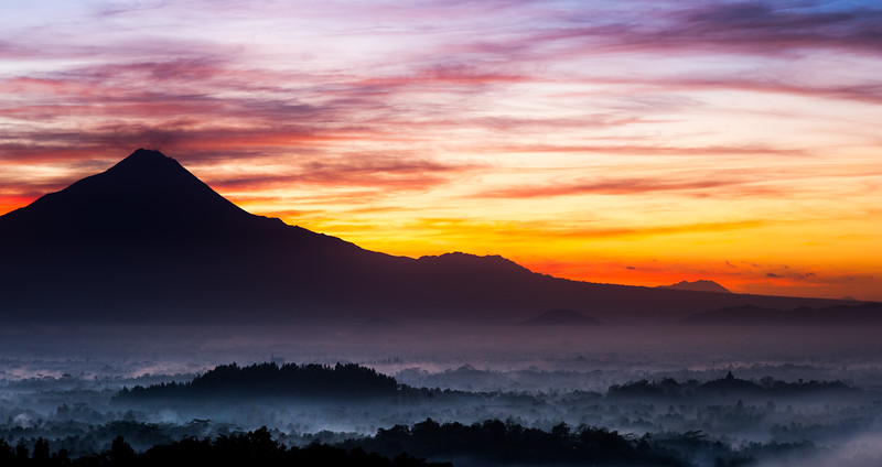 I was filming on the Indonesian island of Java... Early one morning we climbed a hill and waited as the warm glow from the rising sun framed the smouldering volcano of  Merapi. Standing in its shade (to the lower right of this image) is Borobudur, the worlds largest buddhist temple. Once buried deep beneath volcanic ash it is now a UNESCO world heritage centre. #EarthOnLocation #BBCEarth #Volcano #Sunrise #Java #Indonesia #WorldHeritage #Borobudur #Buddhist