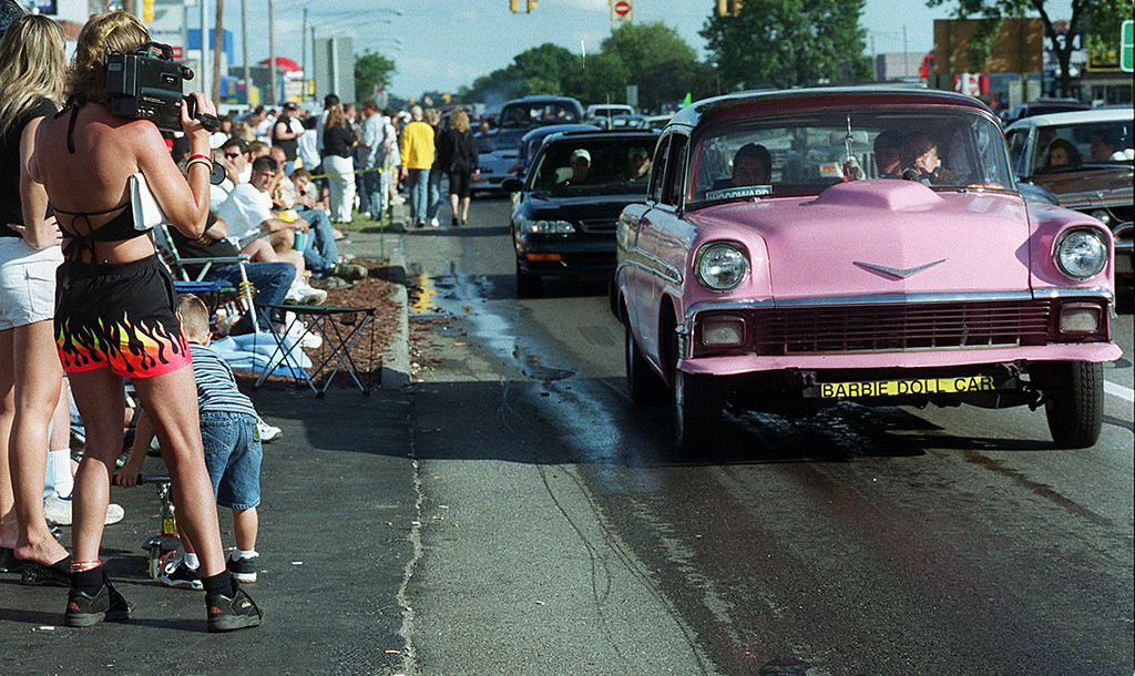 . Brenda Oldeck (left) videotapes the parade of cars up Woodward including this pink Chevy Bel Air during the Dream Cruise 2000 saturday afternoon.