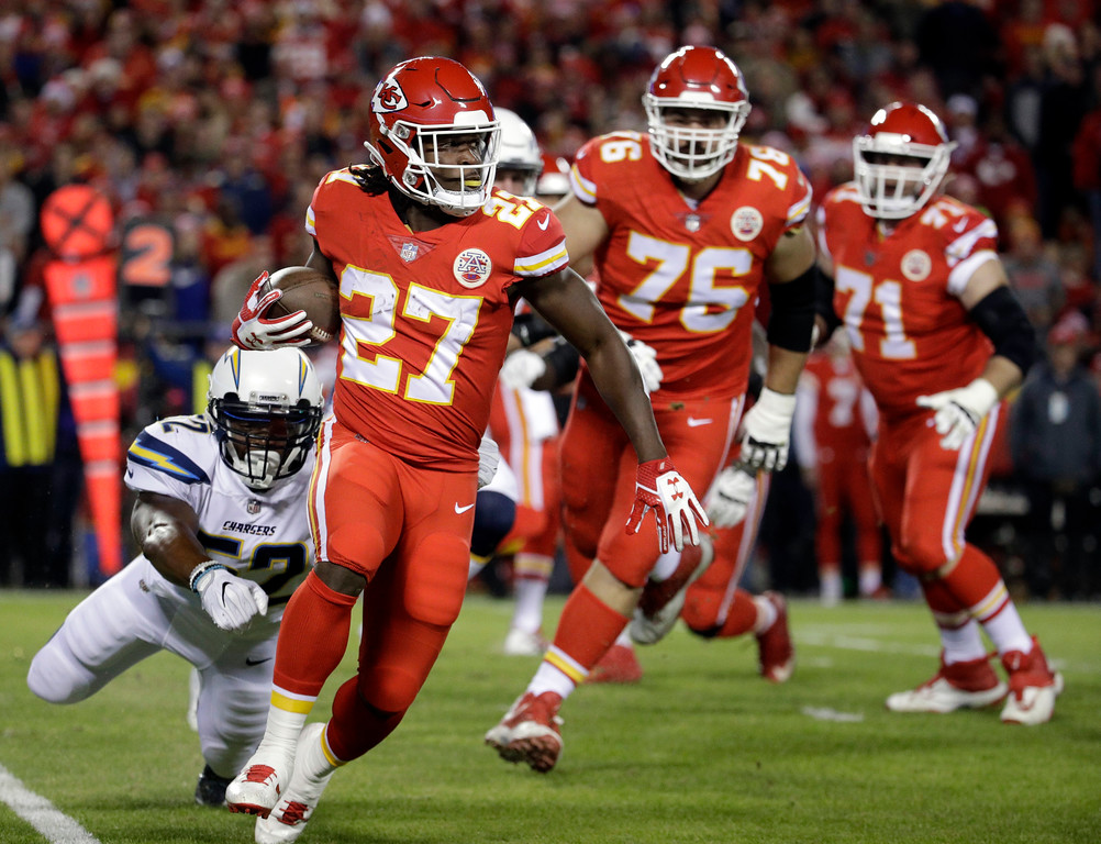 . Kansas City Chiefs running back Kareem Hunt (27) runs past a tackle attempt by Los Angeles Chargers linebacker Denzel Perryman (52) during the first half of an NFL football game in Kansas City, Mo., Saturday, Dec. 16, 2017. (AP Photo/Charlie Riedel)