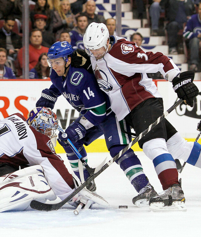 . Vancouver Canucks\' Alexandre Burrows (C) is stopped by Colorado Avalanche goaltender Semyon Varlamov and Ryan O\'Byrne (R) during the first period of their NHL hockey game in Vancouver, British Columbia January 30, 2013.   REUTERS/Ben Nelms