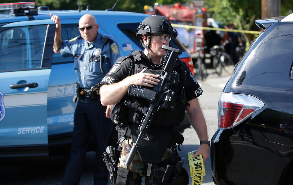 . A Seattle Police SWAT team officer walks with his gun and a roll of police tape at the scene of a shooting Thursday, June 5, 2014 at Seattle Pacific University in Seattle. (AP Photo/Ted S. Warren)