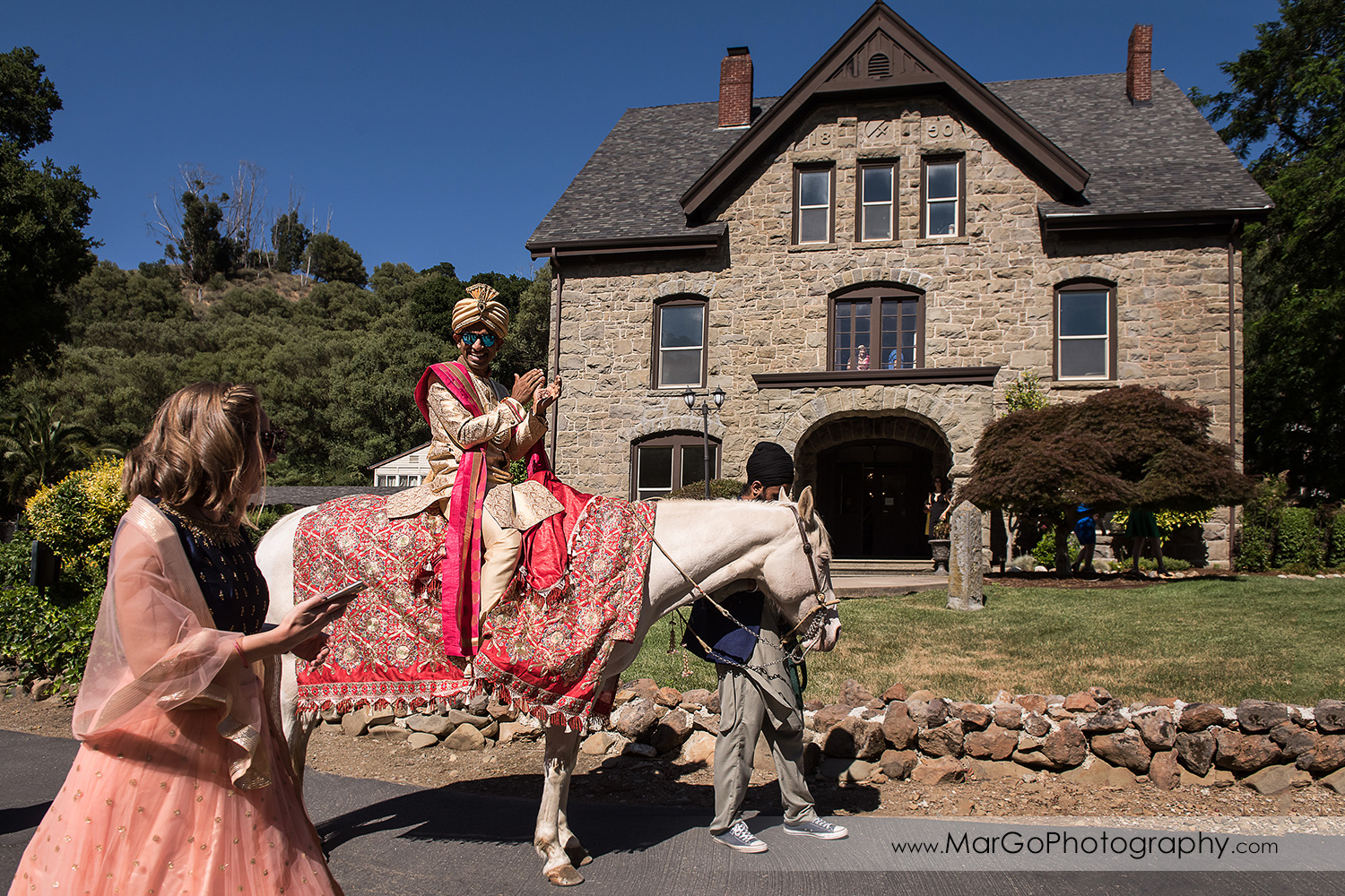 Indian groom on white horse in front of stone building during Baraat Swagat at Elliston Vineyards in Sunol
