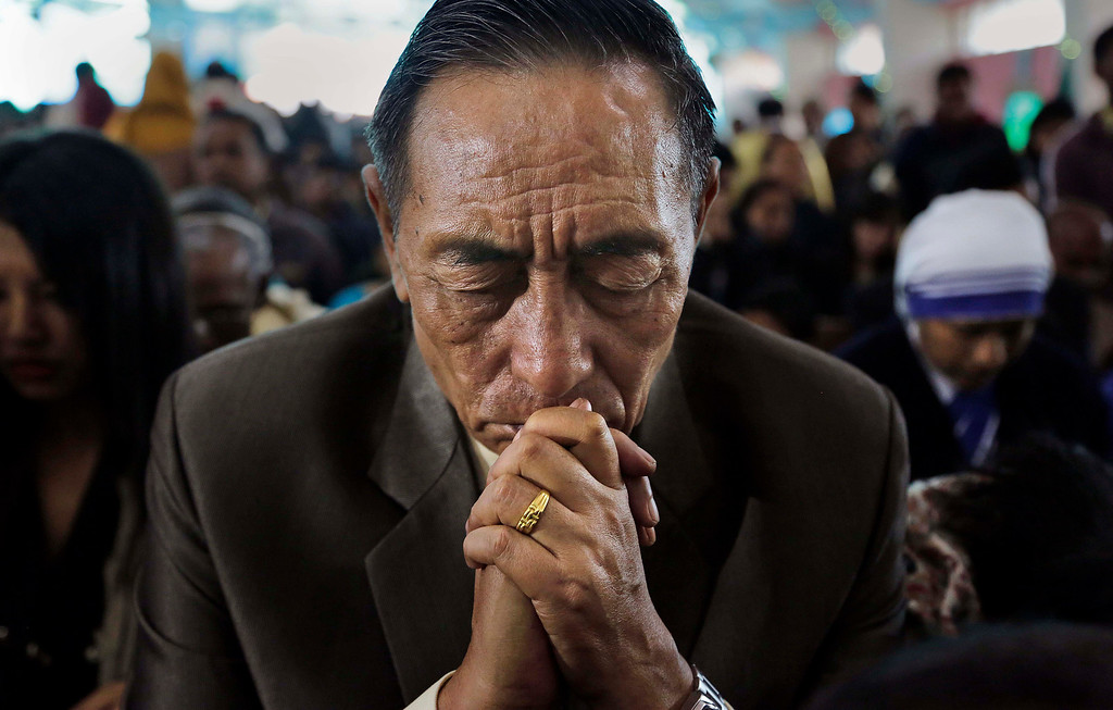 . A Christian man prays during Christmas mass in a church in Gauhati, India, Wednesday, Dec. 25, 2013. Although Christians comprise only two percent of the population among a Hindu majority, the holiday is observed across the country as an occasion to celebrate. (AP Photo/Anupam Nath)