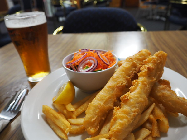 A pub meal of fish and chips, salad and a beer.