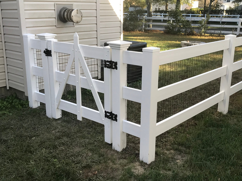3 rail vinyl fence with 4 foot tall black vinyl coated wire for dog containment