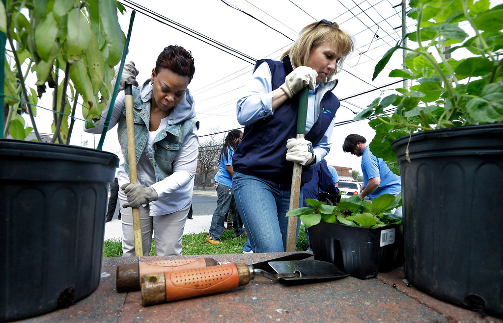 . Camden Mayor Dana Redd, left, and New Jersey Lt. Gov. Kim Guadagno dig holes to plant flowers as part of an Earth Day clean-up effort in Camden, N.J., Tuesday, April 22, 2014. The Earth Day events celebrated on April 22 promote a sustainable and clean environment. (AP Photo/Mel Evans)