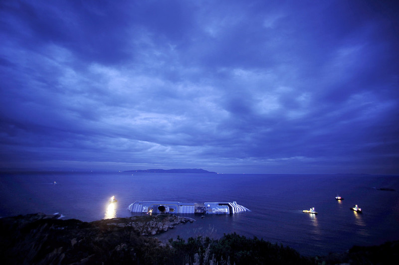 ". Sunset on January 16, 2012, over the cruise liner Costa Concordia aground in front of the harbour of Isola del Giglio after hitting underwater rocks on January 13. Pier Luigi Foschi, head of the Costa Crociere line, said the company had commissioned several firms to look at the best way to salvage the 114,500-tonne vessel lying on its side. The 290-metre (950-feet) long Costa Crociere, which is 17 decks high, has a large gash in its hull from running on to rocks before it capsized on Friday night. Coastguards said the half-submerged giant ship had now stabilised as weather conditions off the Tuscan coast improved but added that there was still a risk the hulk could slip off a rocky shelf into the open sea and sink entirely. ""Costa Concordia crash\"" ranked as Google\'s fifth most searched trending event of 2012. FILIPPO MONTEFORTE/AFP/Getty Images"