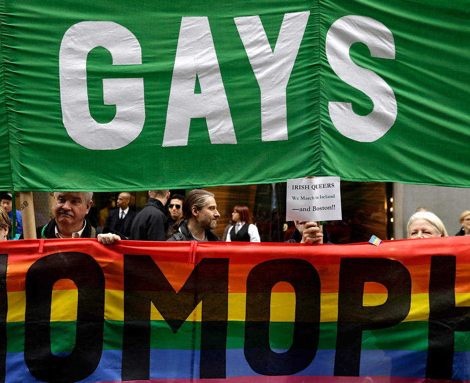 . Protesters hold signs during the St. Patrick\'s Day Parade in New York, Tuesday, March 17, 2015. The group was protesting the exclusion of LGBT groups from the parade. (AP Photo/Seth Wenig)