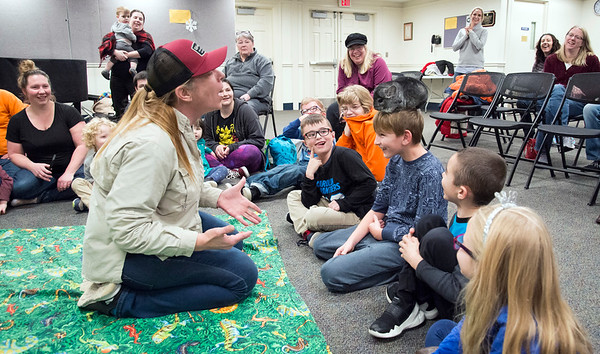 12/30/19 Wesley Bunnell | StaffrrThe Critter Caravan made a stop at the Plainville Public library on Monday night showcasing animals for children to hold and touch. Owner Kathryn Langham tries to get a chinchilla jump from Jakub Hardejuk, age 8, back onto her.