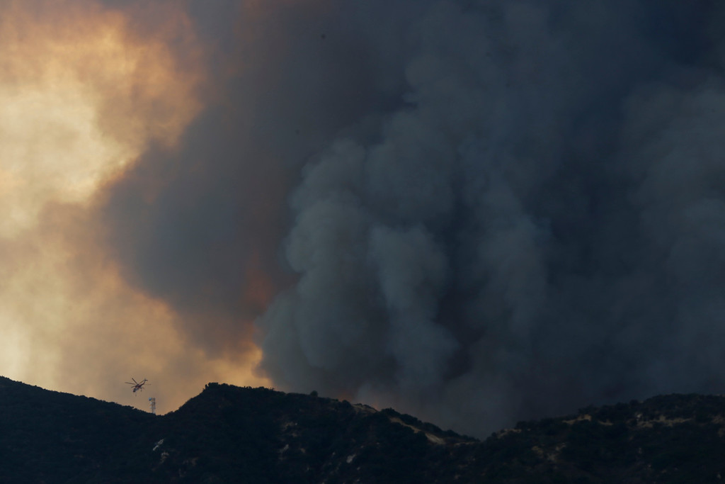 . A fire fighting helicopter is seen under a plume of smoke from the 210 Freeway as a brush fire burns in the Verdugo Mountains in the Sun Valley neighborhood of Los Angeles. (AP Photo/Damian Dovarganes)