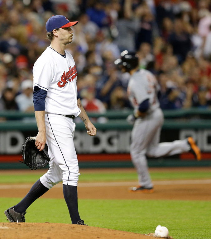 . Cleveland Indians relief pitcher John Axford, left, waits for Detroit Tigers\' J.D. Martinez to run the bases after Martinez hit a three-run home run in the eighth inning of a baseball game, Friday, June 20, 2014, in Cleveland. Tigers\' Miguel Cabrera and Victor Martinez also scored on the hit. (AP Photo/Tony Dejak)