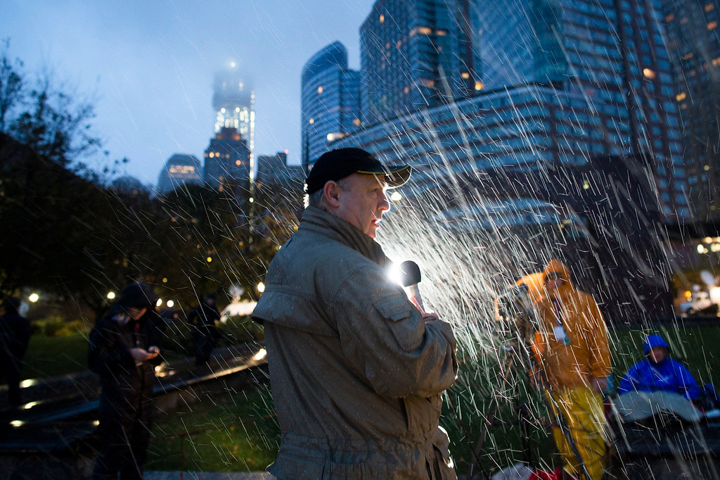 . A news reporter stands in heavy rain as he waits to report live from battery park, Monday, Oct. 29, 2012, in New York. Sandy continued on its path Monday, as the storm forced the shutdown of mass transit, schools and financial markets, sending coastal residents fleeing, and threatening a dangerous mix of high winds and soaking rain.  (AP Photo/ John Minchillo)