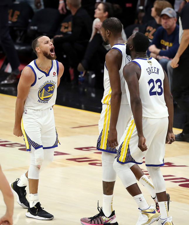 . Golden State Warriors\' Kevin Durant celebrates with Stephen Curry, left, and Draymond Green (23) during the second half of Game 3 of basketball\'s NBA Finals against the Cleveland Cavaliers, Wednesday, June 6, 2018, in Cleveland. The Warriors defeated the Cavaliers 110-102 to take a 3-0 lead in the series. (AP Photo/Carlos Osorio)