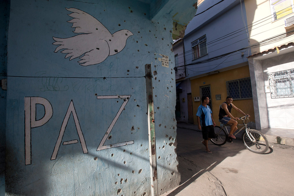 """. Two men walk beside a sign that reads \""""Peace\"""" on a wall covered with holes from bullets of past shootings, during an operation to occupy the Mare slum complex in Rio de Janeiro, Brazil, Saturday, April 5, 2014. More than 2,000 Brazilian Army soldiers moved into the Mare slum complex early Saturday in a bid to improve security and drive out the heavily armed drug gangs that have ruled the sprawling slum for decades. (AP Photo/Silvia Izquierdo)"""