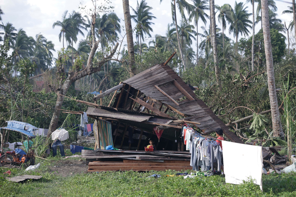Description of . A resident dries their clothes amidst their toppled house at the flash flood-hit village of Andap, New Bataan township, Compostela Valley in southern Philippines Wednesday Dec. 5, 2012. Typhoon Bopha, one of the strongest typhoons to hit the Philippines this year, barreled across the country\'s south on Tuesday, killing scores of people while triggering landslides, flooding and cutting off power in two entire provinces. (AP Photo/Bullit Marquez)