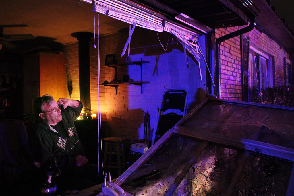 . Gary Buneta takes a phone call as he looks out from his damaged home on Howdershell Road next to Lynn Haven Lane following a strong spring storm in Hazelwood late Wednesday evening, April 10, 2013. Buneta was thrown across rooms when the storm hit.  (AP Photo/Erik M. Lunsford, Post-Dispatch)