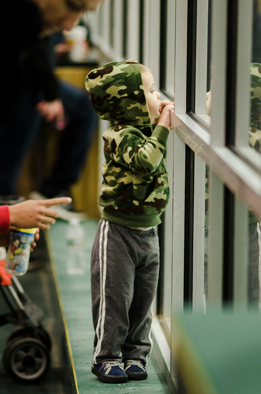 . Jason Fenner, 2, takes a peek at the action during the 2nd Annual Brad Cutting Memorial Ice Hockey Game at the Wallace Civic Center in Fitchburg on Saturday, March 25, 2017.  Cutting was just 20-years-old when he died in a two-car accident on November 27, 2015. SENTINEL & ENTERPRISE / Ashley Green