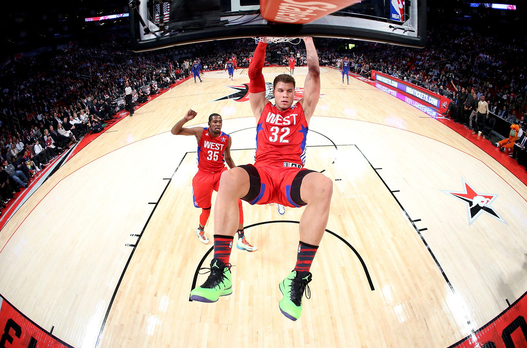 . NBA All-Star Blake Griffin of the Los Angeles Clippers (C) hangs onto the rim after dunking during the 2013 NBA All-Star basketball game in Houston, Texas, February 17, 2013. REUTERS/Ronald Martinez-POOL