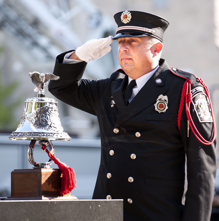 . Champaign Fire Dept. Honor Guard member Curtis Hays salutes after ringing a bell calling all fallen firefighters home who died in the line of duty, at a 9/11 remembrance ceremony hosted by the Champaign Fire and Police departments at West Side Park in Champaign, Ill., on Wed. Sept. 11, 2013. (AP Photo/News-Gazette/John Dixon)