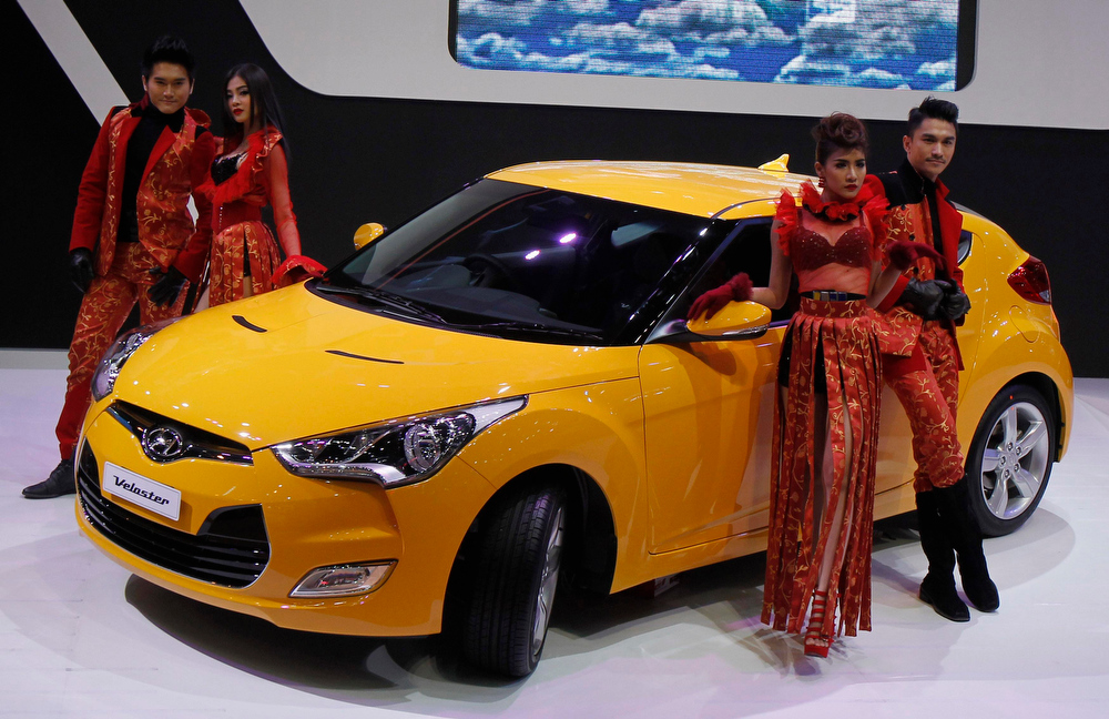 . Models pose beside a Hyundai Veloster during a media presentation of the 34th Bangkok International Motor Show in Bangkok March 26, 2013. The Bangkok International Motor Show will be held from March 27 to April 7. REUTERS/Chaiwat Subprasom