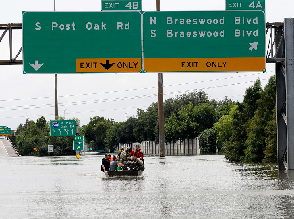 . Residents are rescued from their homes surrounded by floodwaters from Tropical Storm Harvey on Sunday, Aug. 27, 2017, in Houston, Texas. (AP Photo/David J. Phillip)