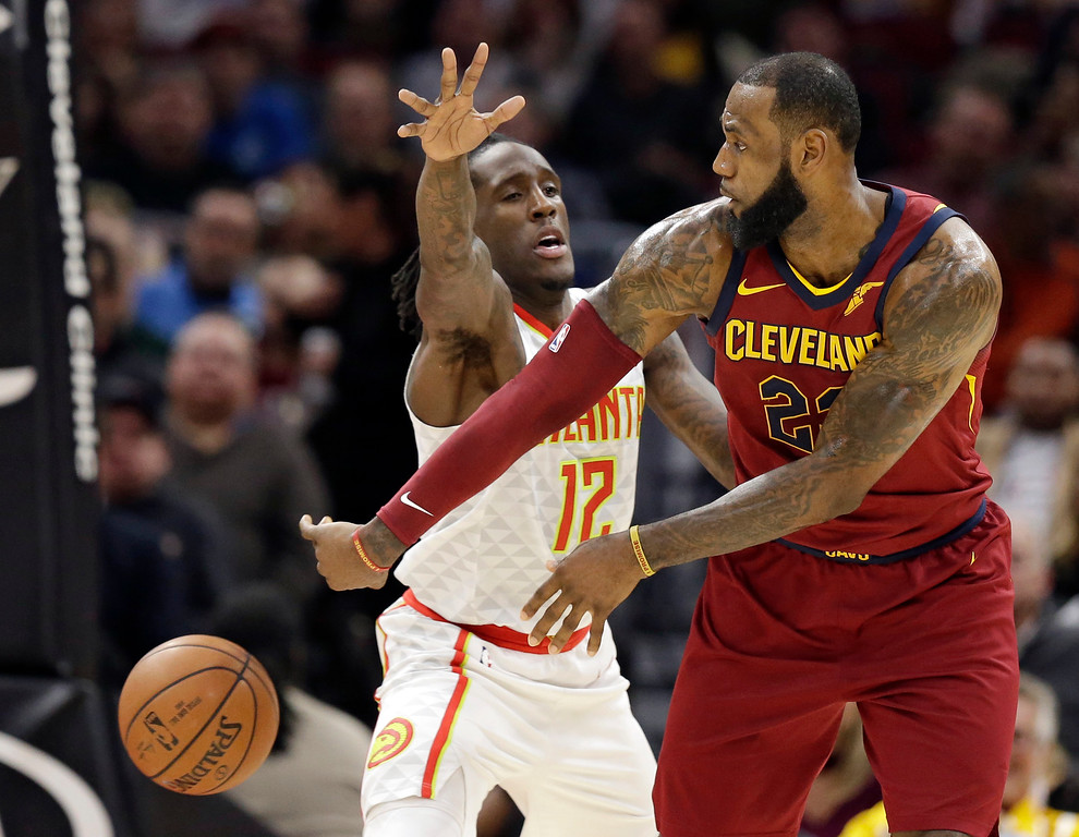. Cleveland Cavaliers\' LeBron James, right, passes against Atlanta Hawks\' Taurean Prince in the first half of an NBA basketball game, Tuesday, Dec. 12, 2017, in Cleveland. (AP Photo/Tony Dejak)