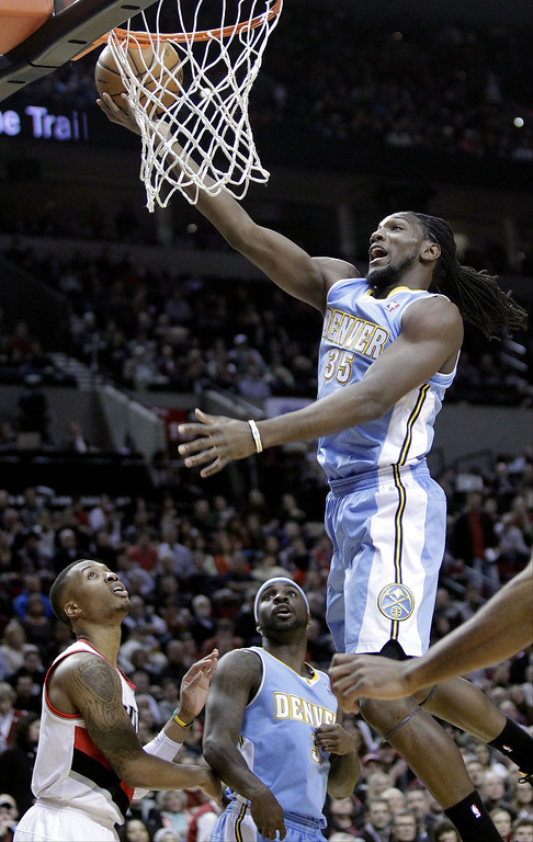 . Denver Nuggets forward Kenneth Faried, right, goes to the hoop over Portland Trail Blazers guard Damian Lillard, left, and Denver Nuggets guard Ty Lawson during the first half of an NBA basketball game in Portland, Ore., Thursday, Jan. 23, 2014. (AP Photo/Don Ryan)