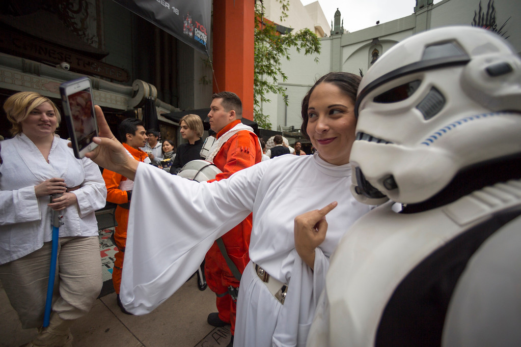 ". Costumed fan Natalie Benavides, dressed as Princess Leia, in honor of actress Carrie Fisher, who played Leia in the ""Star Wars\"" movie series, takes a selfie at a memorial in the forecourt at the TCL Chinese Theatre in the Hollywood section of Los Angeles, Saturday, Dec. 31, 2016. Fisher had been hospitalized since Dec. 23 after falling ill aboard a flight and being treated by paramedics at the Los Angeles airport. One day after Fisher\'s death, her actress mother, 84-year-old Debbie Reynolds, died as well. A joint funeral for the two women has been announced. (AP Photo/Damian Dovarganes)"