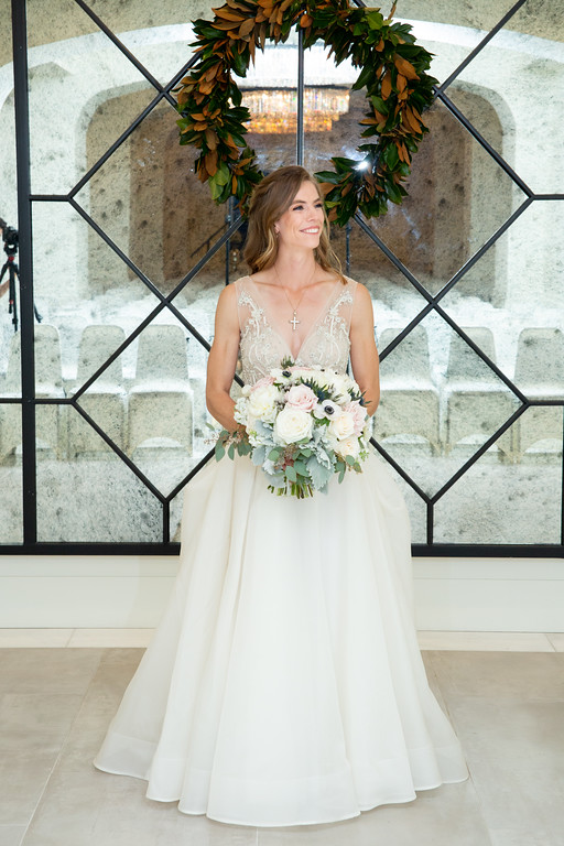 bride wearing an offwhite lace wedding dress standing green wreth holding a white rose boquette