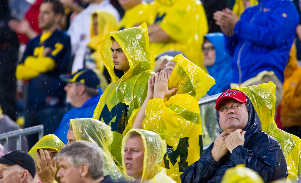 . Michigan and Utah fans wear rain gear before inclement weather suspended a an NCAA college football game between the schools in the fourth quarter, in Ann Arbor, Mich., Saturday, Sept. 20, 2014. (AP Photo/Tony Ding)
