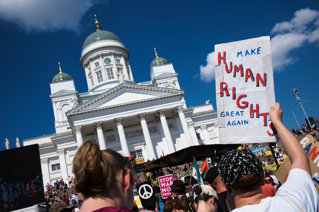 . A woman shows a poster as she attends a rally against the policy of U.S. President Donald Trump and Russian President Vladimir Putin in central Helsinki, Sunday, July 15, 2018. President Trump and President Putin will meet in Finland\'s capital on Monday, July 16, 2018. (AP Photo/Markus Schreiber)