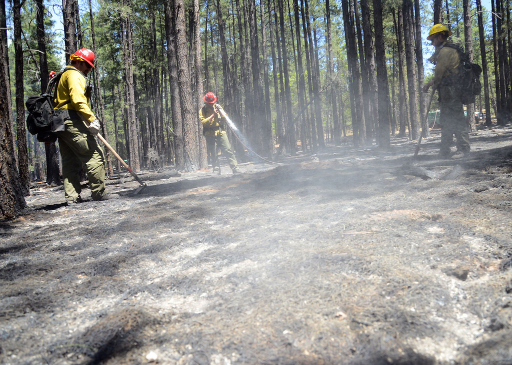 . U.S. Forest Service firefighting crews work hotspots Thursday May 22, 2014 near Sedona, Ariz.The human-caused Slide Fire started Tuesday. (AP Photo/Vyto Starinskas)