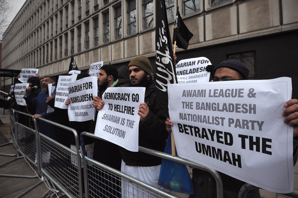 . Muslim protesters hold signs against the Bangladeshi government as they protest outside the embassy of Bangladesh in central London on March 1, 2013, a day after the vice president of Jamaat-e-Islami party was found guilty of murder, religious persecution and rape by a war crimes tribunal. Fresh clashes erupted in Bangladesh, bringing the number of people killed to 52 in violence triggered by convictions for Islamist leaders over war crimes committed during the 1971 independence war.   CARL COURT/AFP/Getty Images
