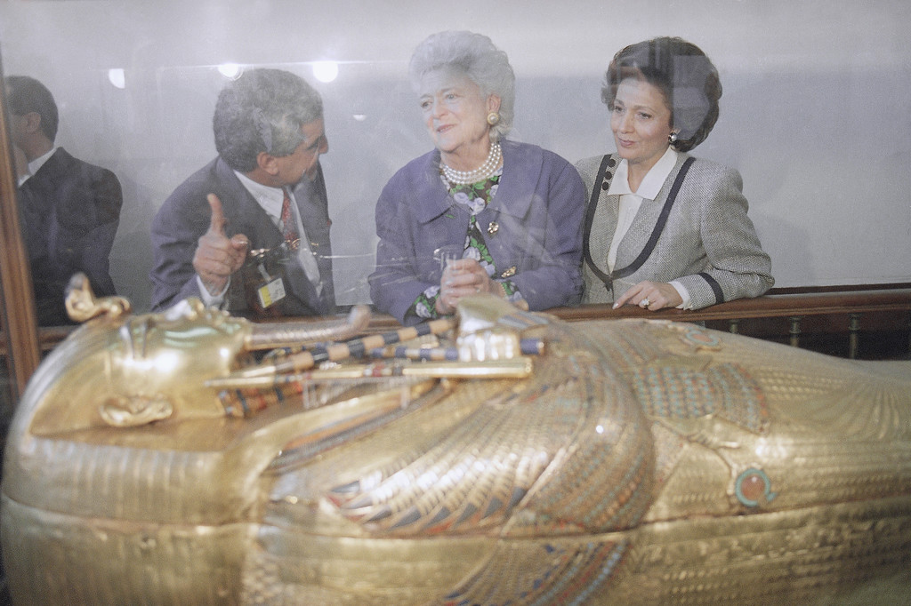 . U.S. first lady Barbara Bush, center, accompanied by her Egyptian counterpart Suzanne Mubarak, right, is given a tour of the Tutankhanum collection by Zahi Hawass, an Egyptologist, at the Egyptian Museum in Cairo, Friday, Nov. 23, 1990. This photo was taken through the glass cover of King Tut\'s gold coffin. Later in the day President and Barbara Bush travel to Geneva to meet Syrian President Hafez El- Assad. (AP Photo/Tracie Cambre Pierce)