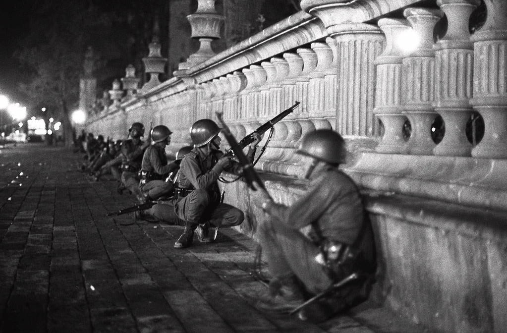 . Mexican army soldiers crouch with weapons ready  in Mexico City\'s Tlatelolco district, in this October 2, 1968  photo.  The truth behind the stunning assault on a peaceful democracy protest known as the Tlatelolco Massacre in which some 300 people are believed to have been killed remains largely hidden by government and military secrecy. (AP Photo/STR)