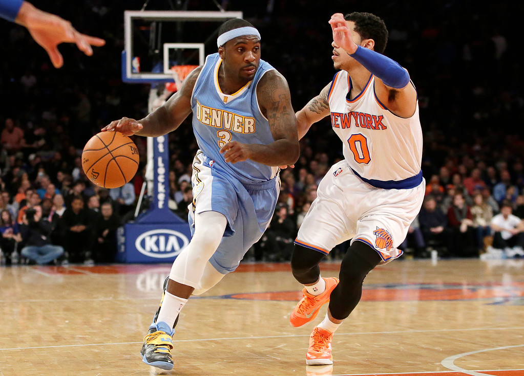 . Denver Nuggets guard Ty Lawson (3) drives to the basket with New York Knicks guard Shane Larkin (0) defending in the first half of an NBA basketball game at Madison Square Garden in New York, Sunday, Nov. 16, 2014. (AP Photo/Kathy Willens)