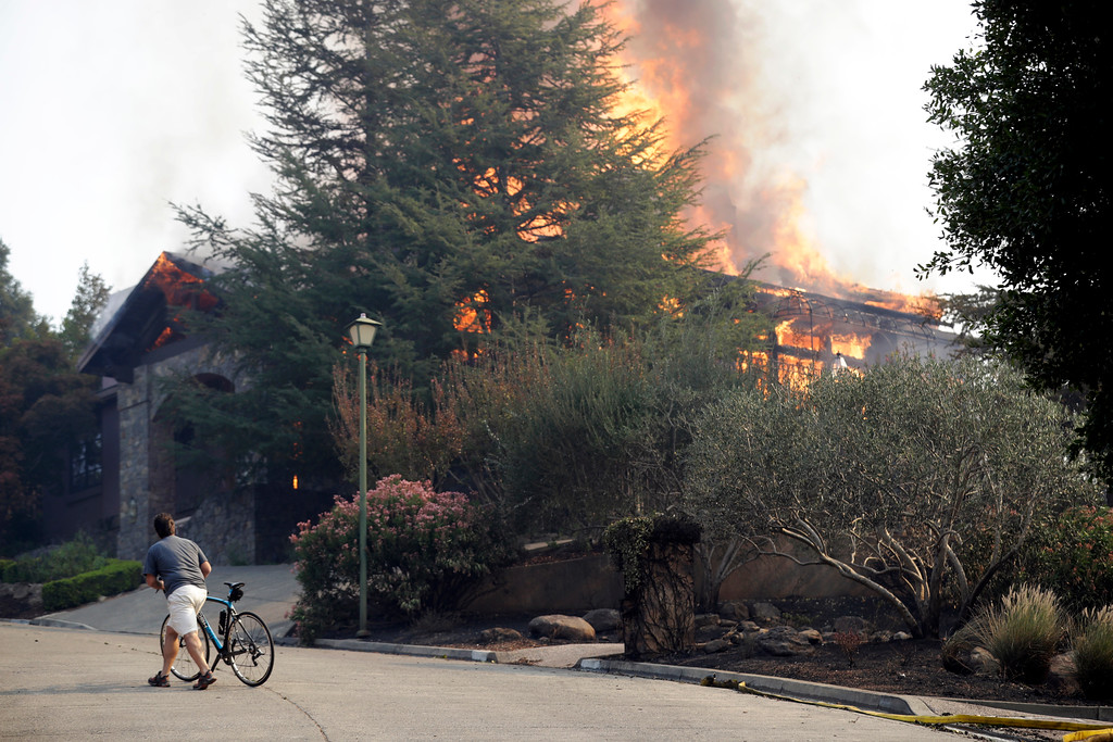 . A man walks next to a burning house in Silverado Crest subdivision Monday, Oct. 9, 2017, in Napa, Calif. Wildfires whipped by powerful winds swept through Northern California sending residents on a headlong flight to safety through smoke and flames as homes burned. (AP Photo/Marcio Jose Sanchez)